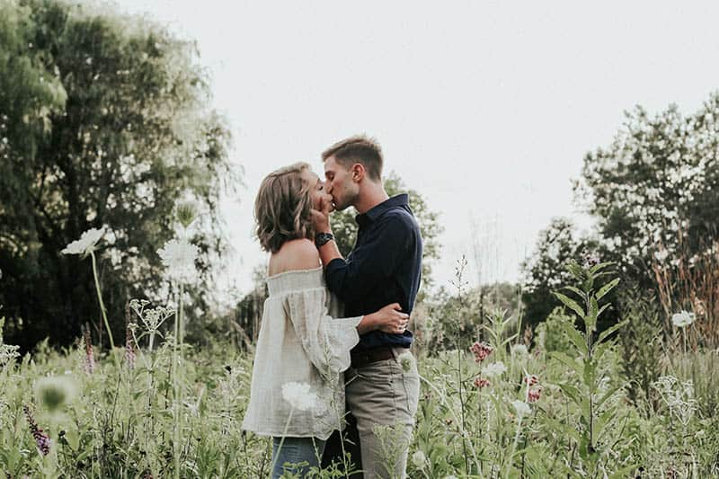 romantic couple standing and kissing on grass field