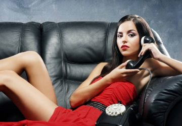 hot woman in red dress holding a wired old phone