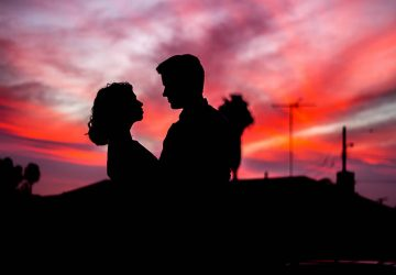 silhouette of man and woman looking each other outside