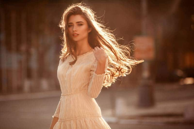 Beautiful young lady with long hair and cute dress on the street