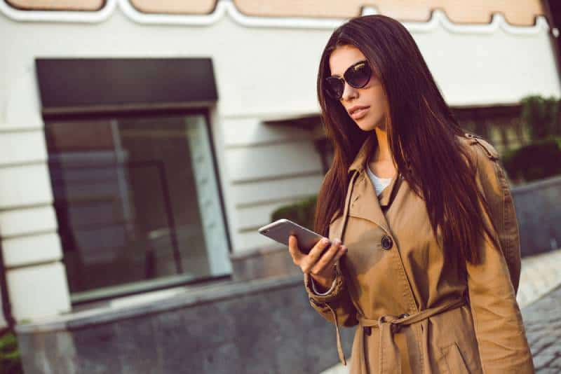 Beautiful young woman in trench using her mobile phone