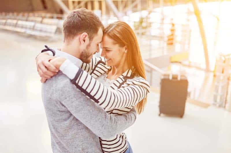 Happy couple hugs each other at the airport