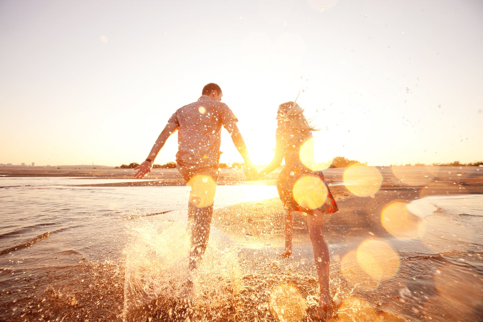 a man and a woman run along the beach holding hands