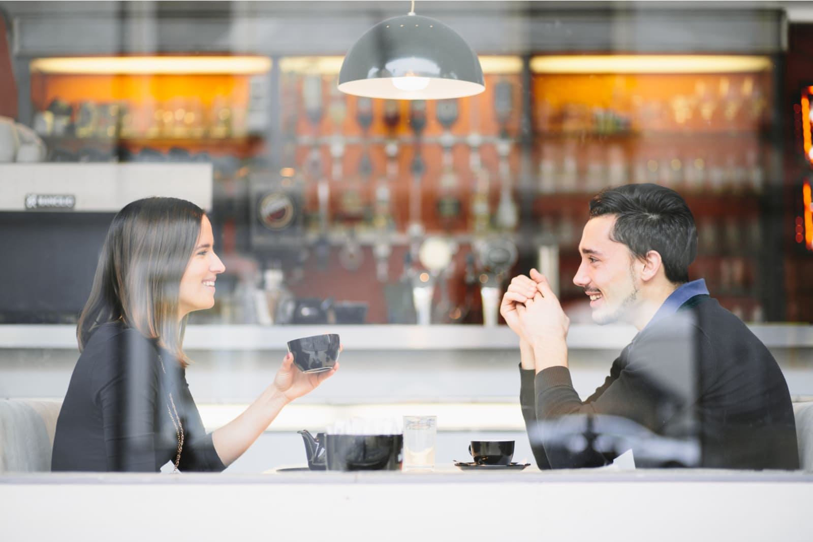 a man and a woman sit and drink coffee