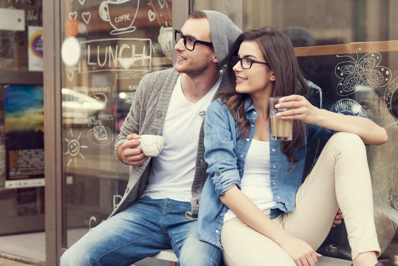 a man and a woman sit drinking coffee and looking away