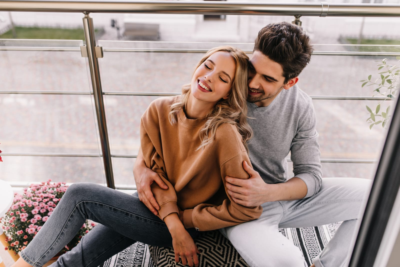 a man and a woman sit on the balcony embracing and laughing
