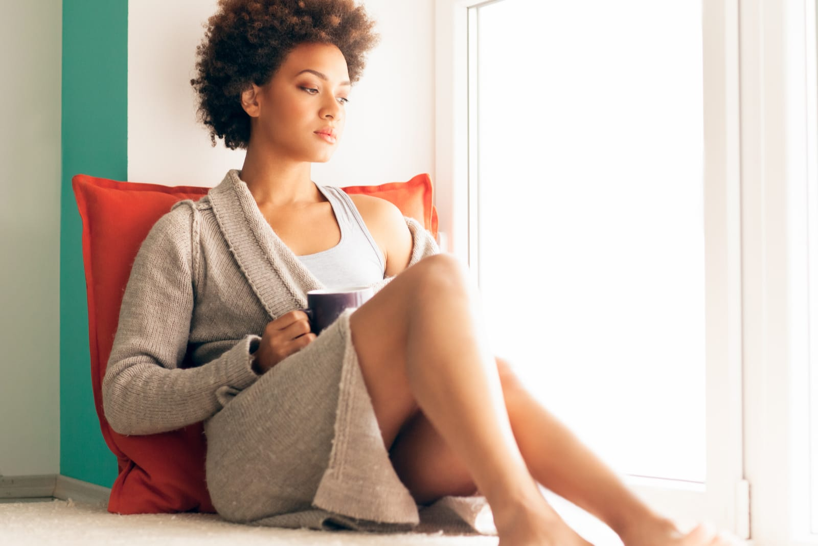 a woman with a cup of coffee is sitting by the window