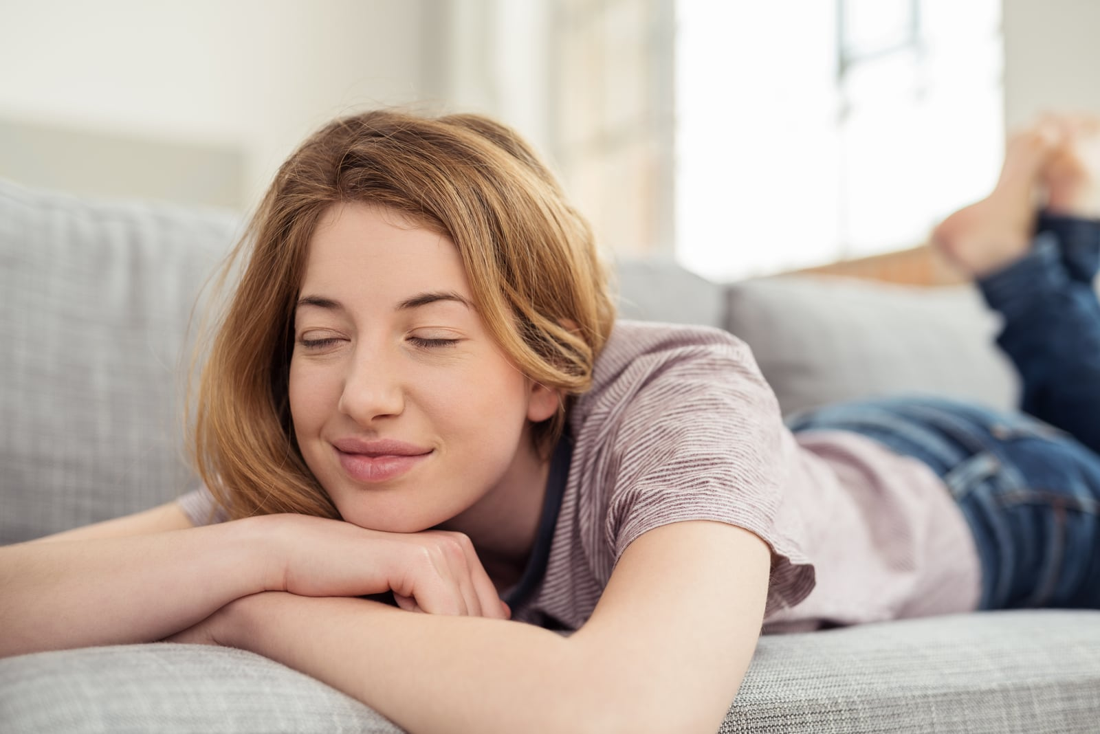 a young woman is lying and enjoying herself on the couch