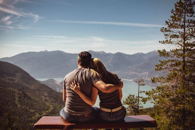 back view of couple hugs on bench and looking at lake