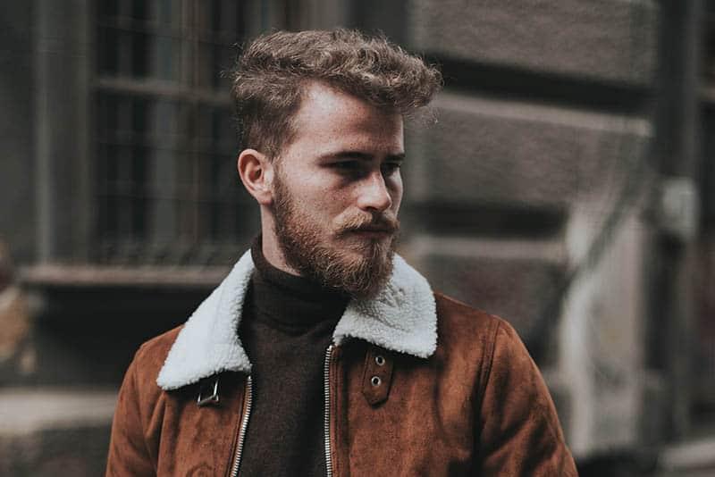 bearded man wearing brown jacket outside