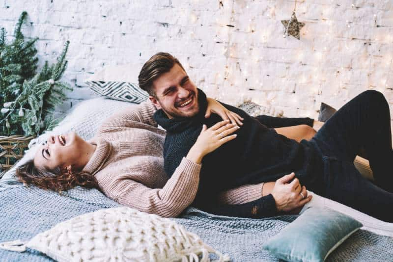 cheerful man and woman lying on bed