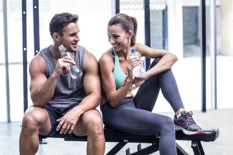 couple drinking water and sitting at gym