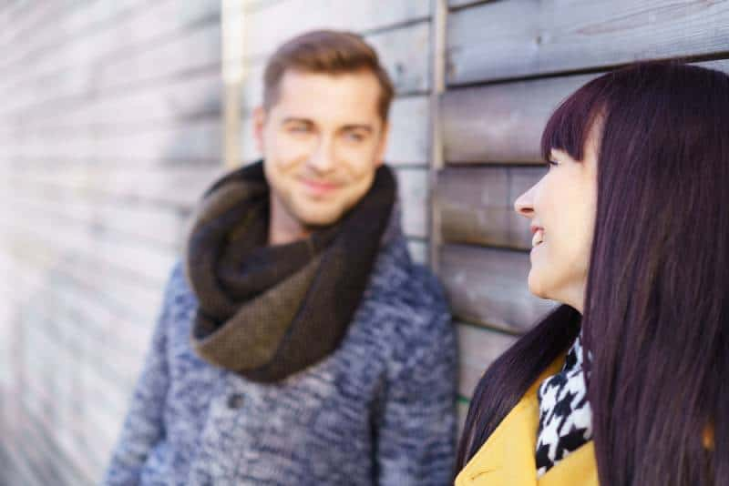 cute woman standing outside looking at man with a warm smile