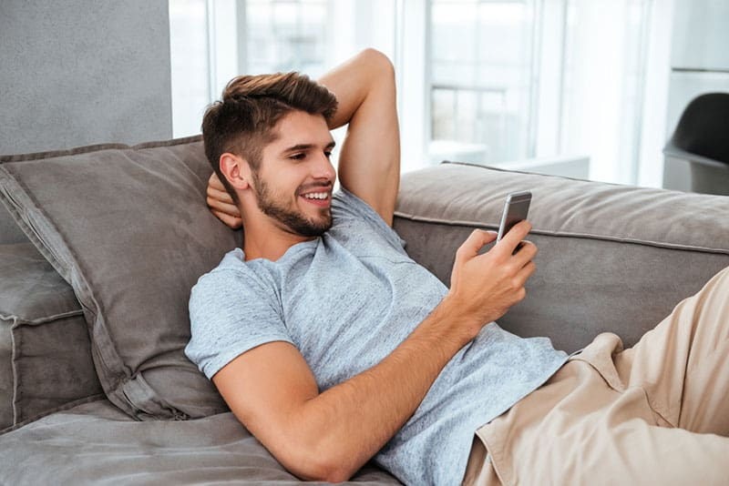 happy man looking at mobile phone