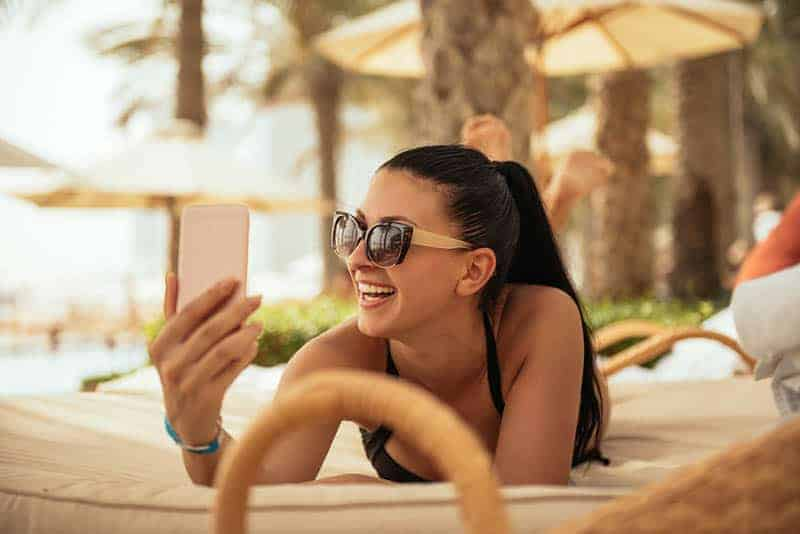 happy woman wearing sunglasses and looking at phone