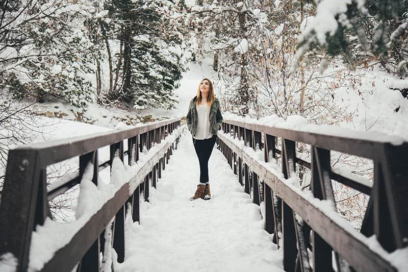 Young woman standing on a snowy bridge