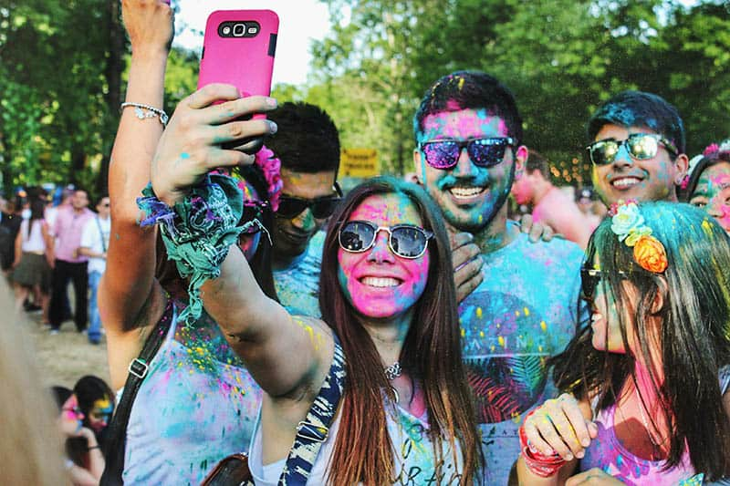Young people covered with paint taking selfie