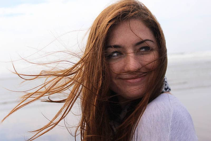 Girl with wind in her hair smiling on beach