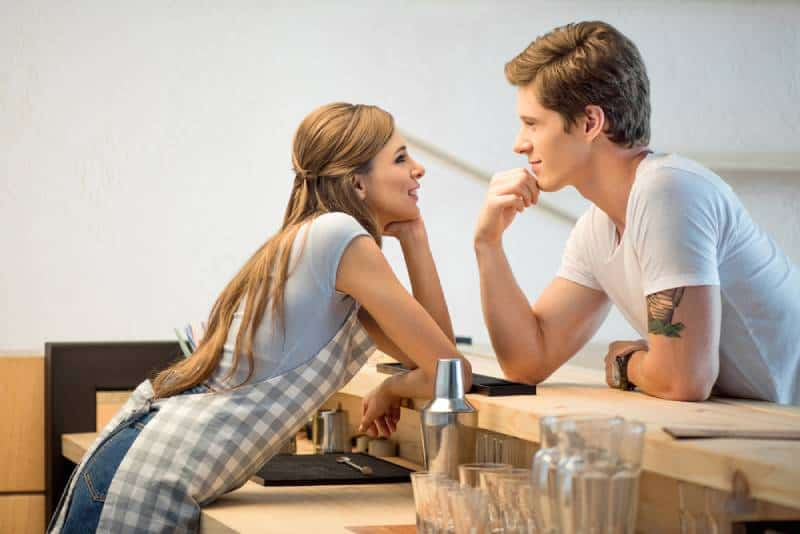 man and woman flirting while working in cafe