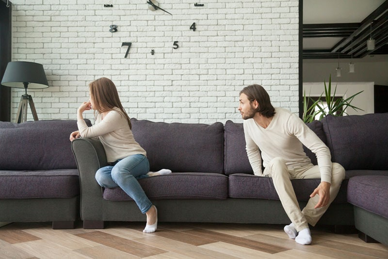 man blaming woman and arguing on the couch
