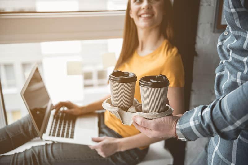man brings coffee to woman
