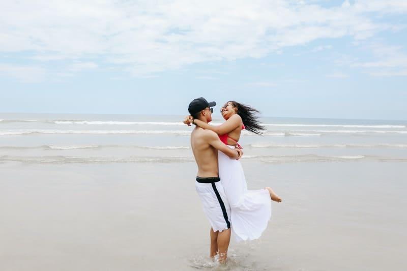 man carrying woman near sea
