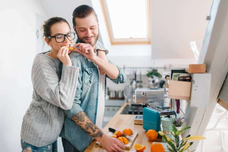 man giving piece of orange to his girlfriend at the kitchen
