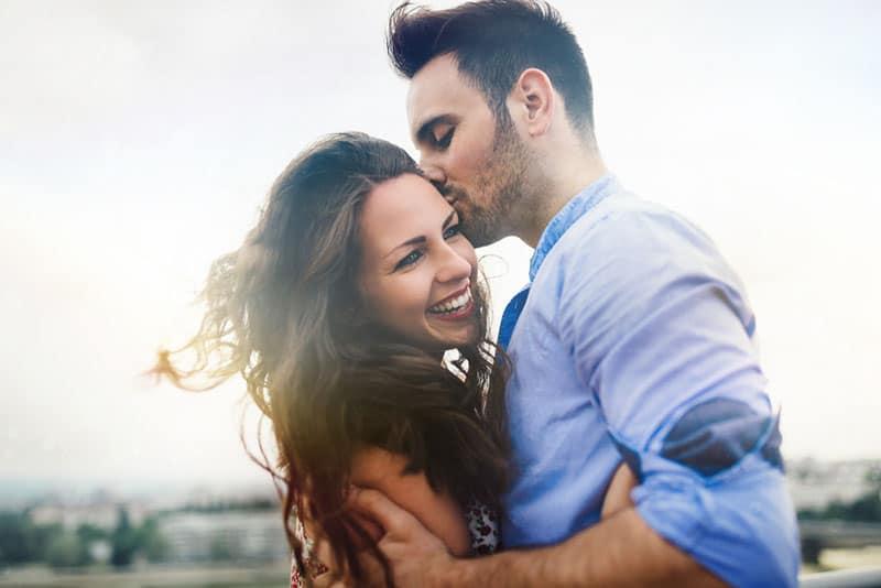 man kissing a happy woman