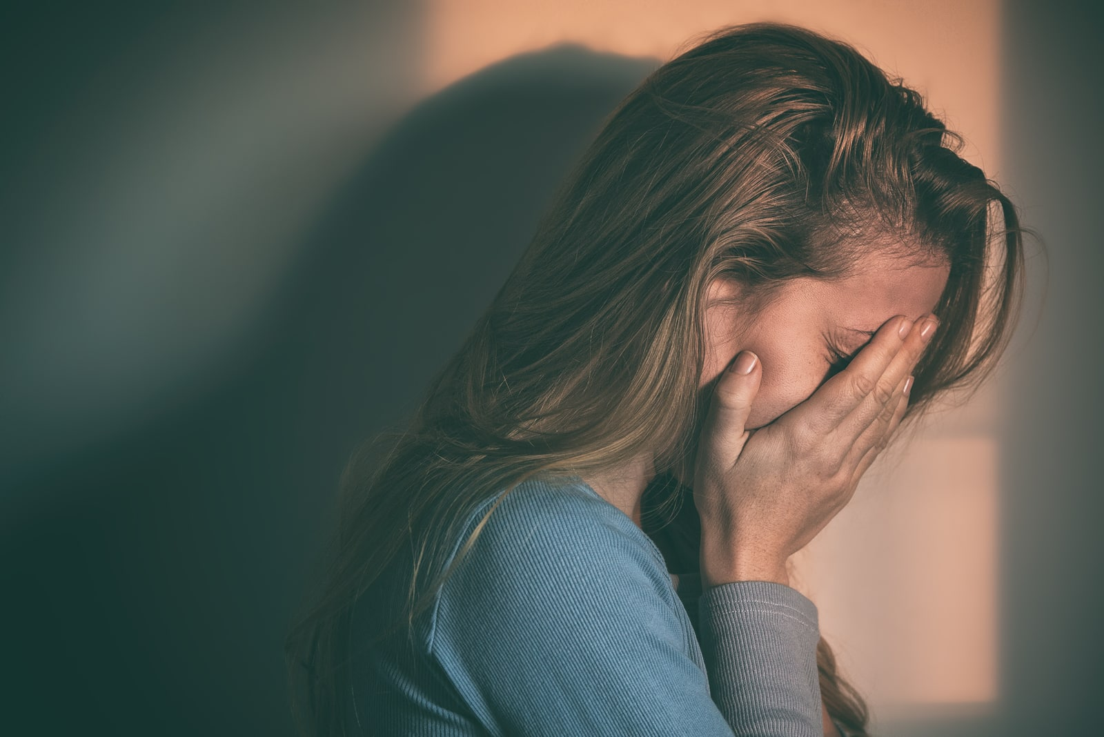 sad young woman holding hands on her face