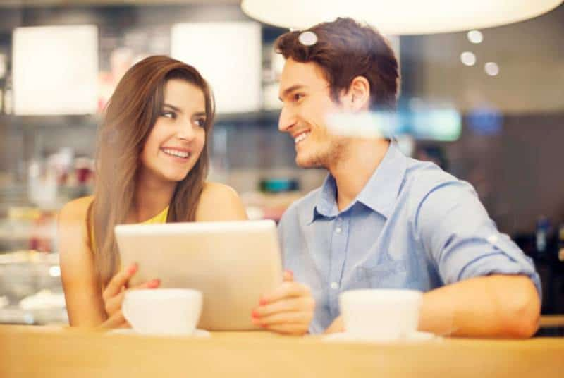 smiling couple sitting and looking at each other in cafe