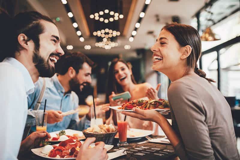 smiling friends at restaurant