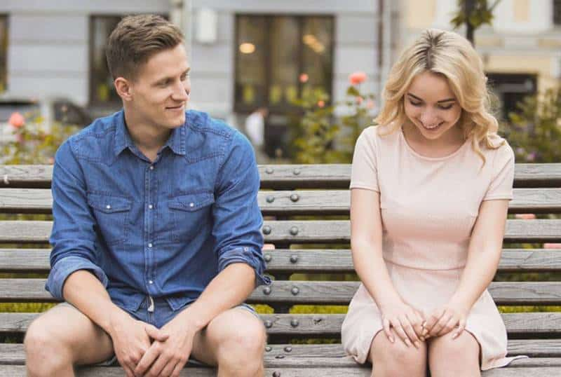 smiling man and woman sitting on a park bench