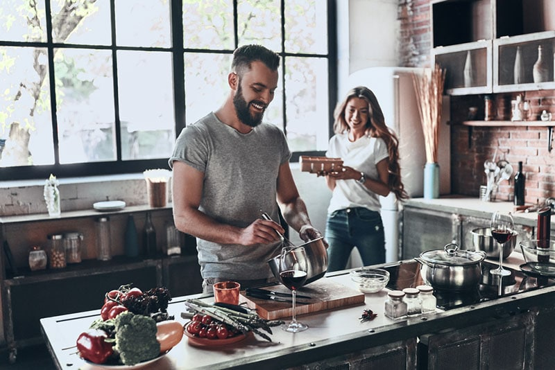 smiling man cooking with woman