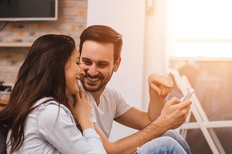 smiling man showing something on his phone to smiling woman