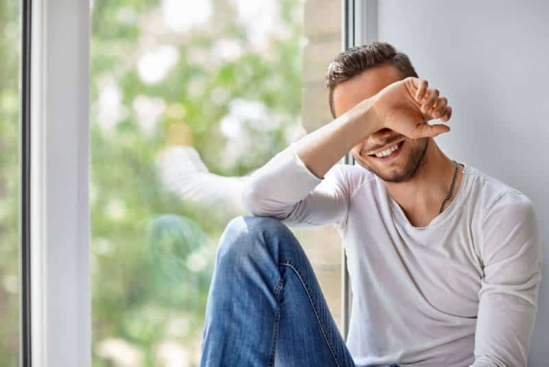 smiling shy man close face with hand while sitting beside window