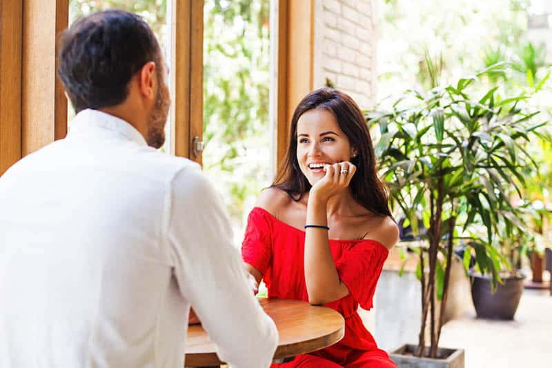 smiling woman in red dress looking at man