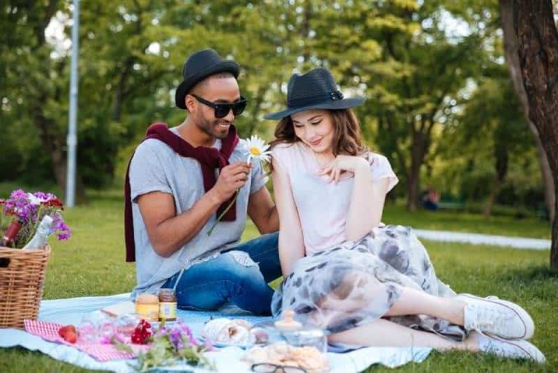 smiling young man giving flower to his shy girlfriend on picnic