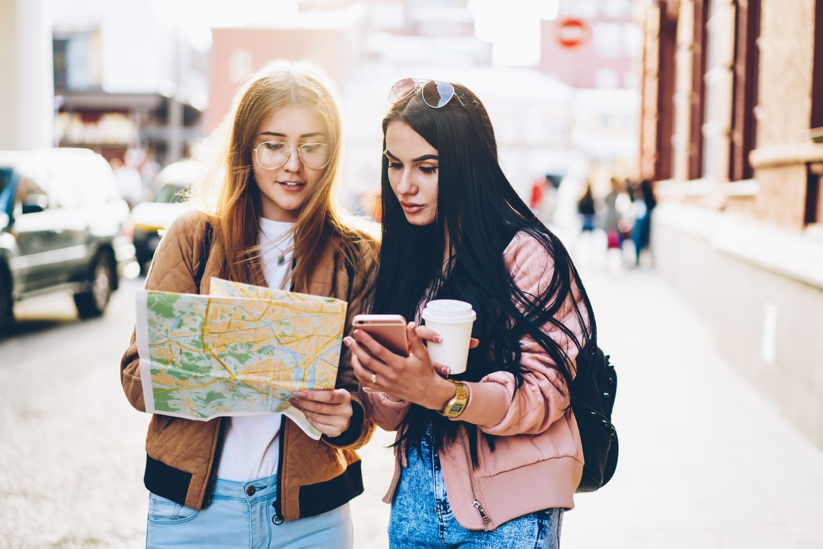 two friends on the street looking at a map