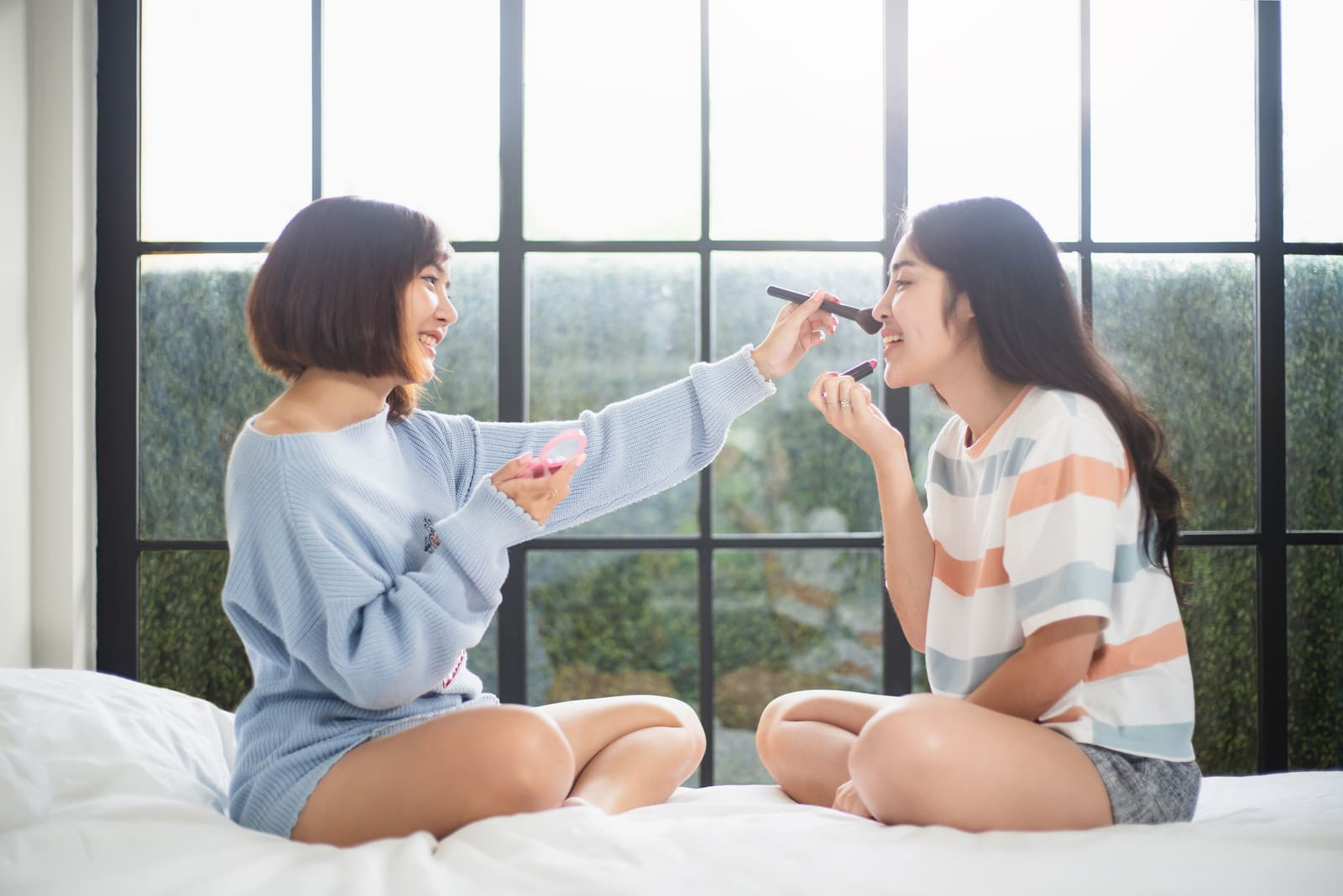 two friends sit on the bed and put on makeup
