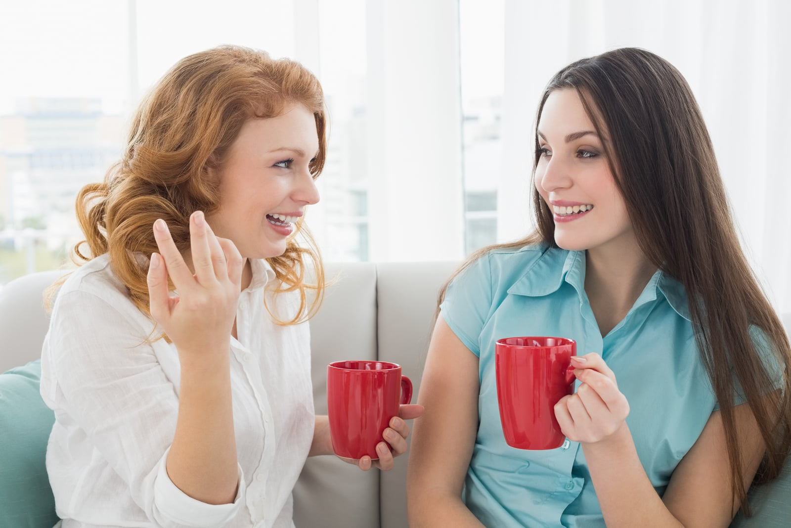 two smiling friends talking and drinking coffee