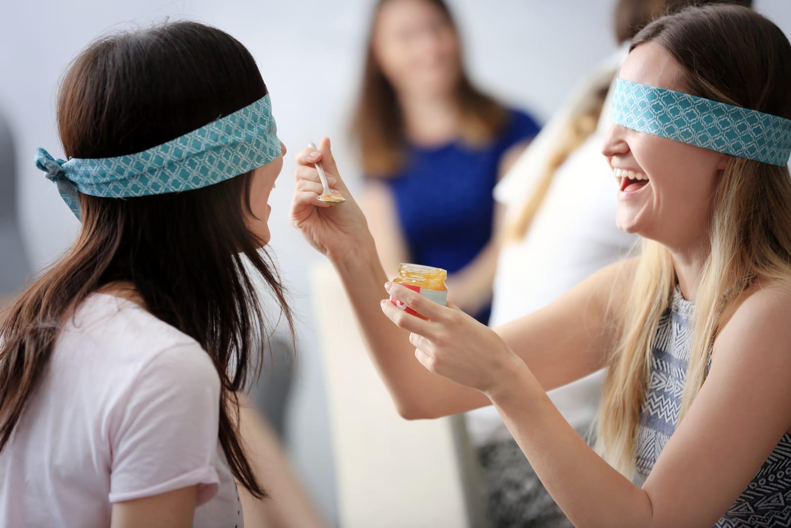 two women taste food blindfolded