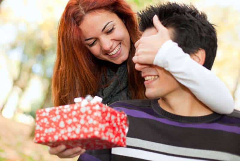 woman giving present to her man while covering his eyes
