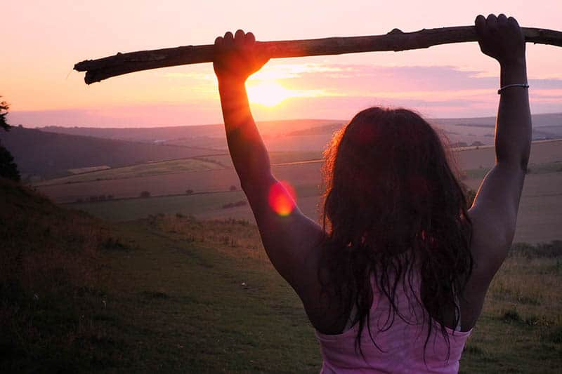 woman holds wooden branch up and looking at sunset
