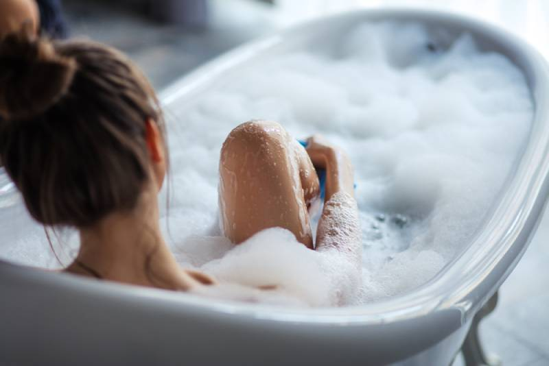 woman massaging her leg in the tub
