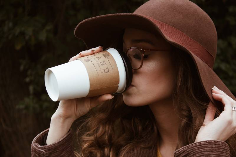 woman wearing brown hat and drinking coffee from cup