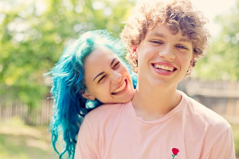woman with blue hair smiling with her boyfriend