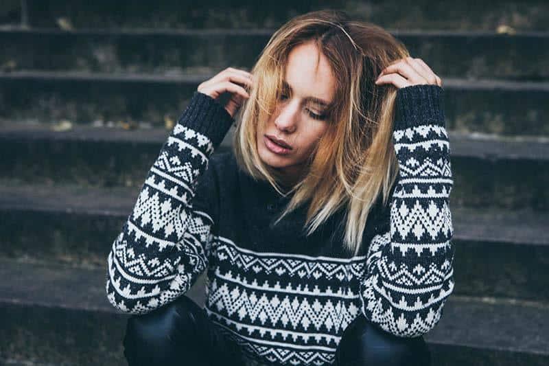 worried woman in sweatshirt sitting on stairs outside