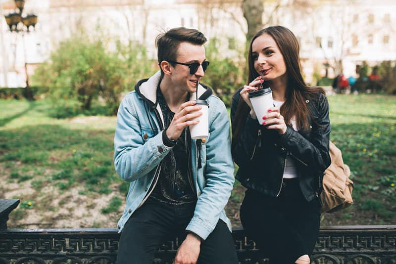 young couple drinking coffee in the park