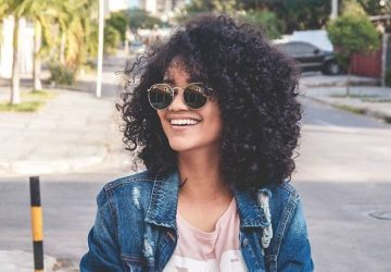afro woman wearing sunglasses and smiling outside
