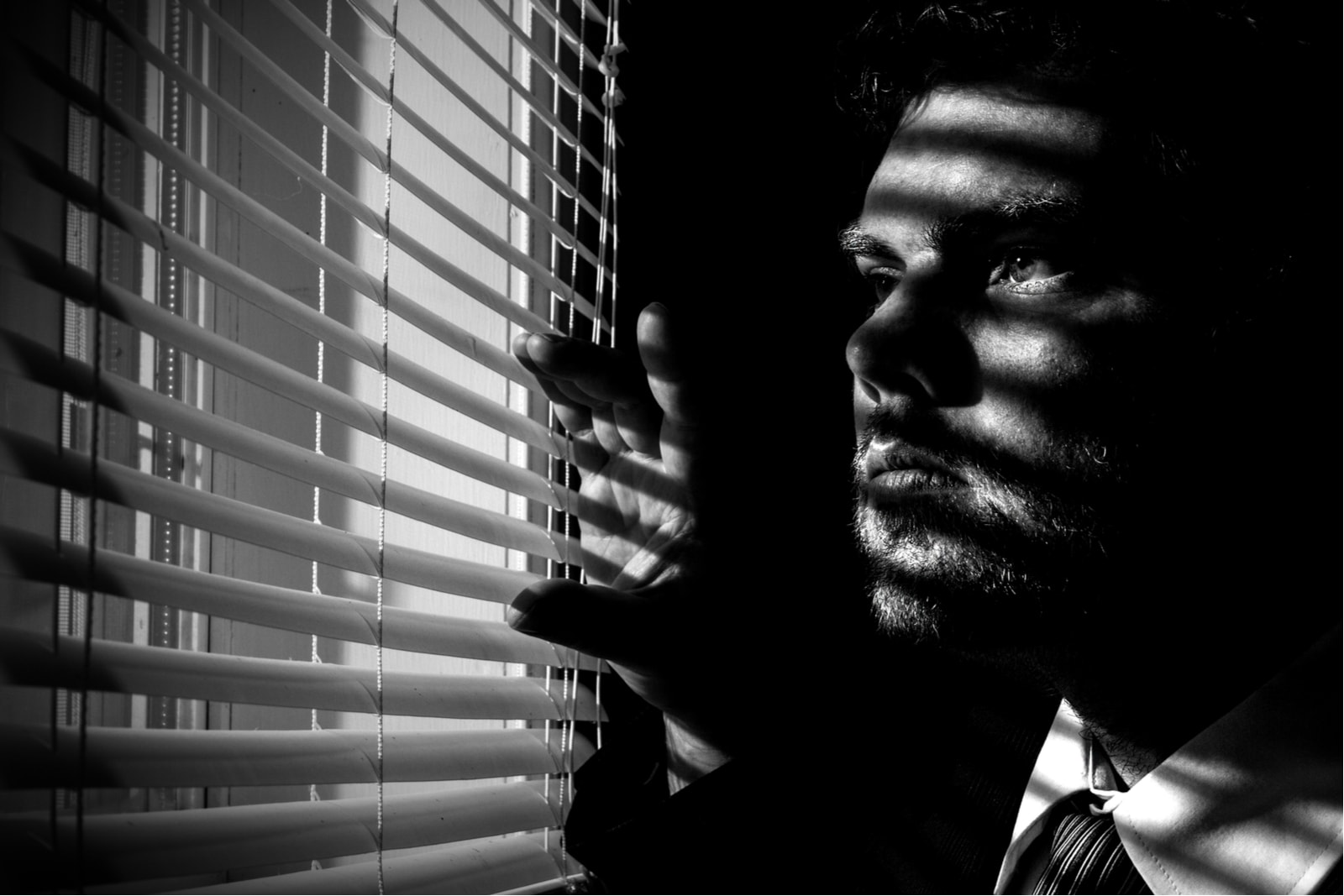 a man from a dark room peeks through the blinds